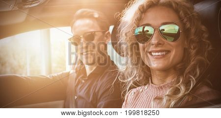 Portrait of smiling couple doing test drive in car
