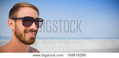 Fashionable man wearing sun glasses  against promenade by sea against clear sky