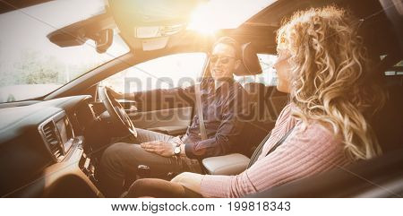 Couple talking while sitting in car during test drive