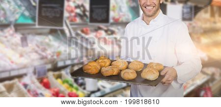 Baker showing bread against white background  against vegetables at grocery store