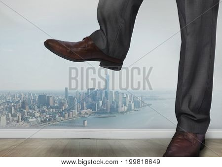 Digital composite of Businessman's feet and shoes stamping on city