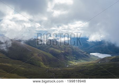 River Descending Scottish Highland Mountain Valley To Lake Under Clouds