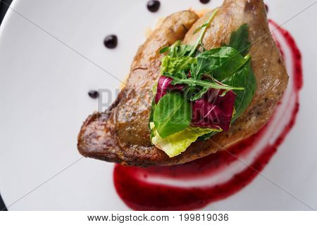 Exclusive restaurant meals. Duck confit with braised cabbage, baked apple and cranberry sauce served on snow white plate with cutlery on black table background, copy space, top view, closeup