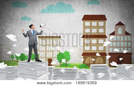 Businessman in suit standing among flying paper planes with speaker in hand with sketched cityscape view on background. Mixed media.
