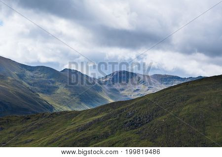 Scottish Highland Hillsides In Shifting Colours Against Cloudy Sky Background