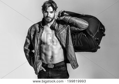man or bearded macho guy with naked torso holds big bag in fashionable leather jacket and pants black and white poster