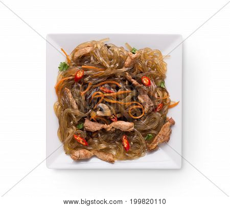 Asian restaurant healthy food delivery. Funchoza with meat and vegetables, soy sauce, chilli pepper and cilantro on square platter isolated on white background, top view