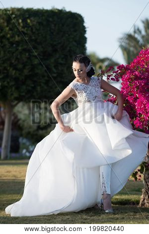 Girl bride with adorable face in beautiful wedding bridal white dress and trousers high heels shoes holding full skirt in hands posing on background blooming bush with pink flowers and green leaves