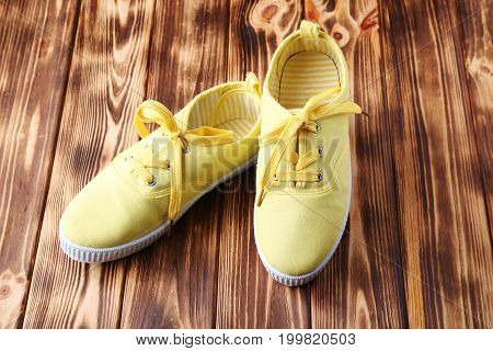 Yellow sneakers with shoelace on brown wooden table