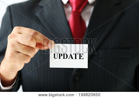 Businessman holding card with the word Update