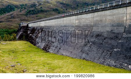Hydroelectric Power Water Dam Wall In Concrete Between Mountain Hillsides