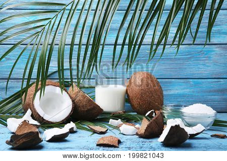 Coconuts With Leafs And Bottle Of Milk On Blue Wooden Table