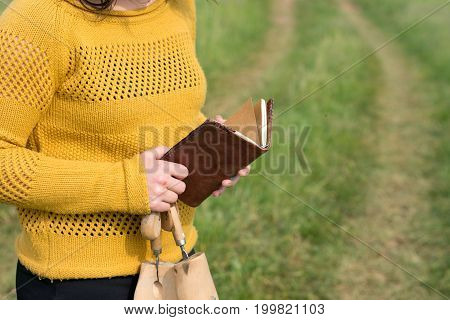 The girl stands on a meadow with a leather notebook and a shoemaker's hoof
