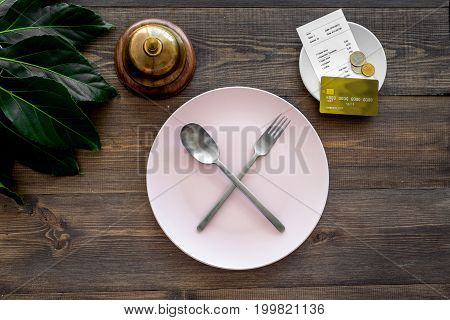 Ask for the bill at restaurant. Service bell near plate whith crossed spoon and fork on wooden table top view.