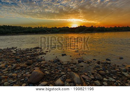 Clouds over the river painted by orange color of sunrise. The wood and stones ashore still dark but are visible rather well.