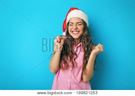 Portrait of young woman in santa hat on blue background