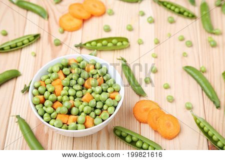 Green Peas And Carrots Sliced In Bowl On Wooden Table