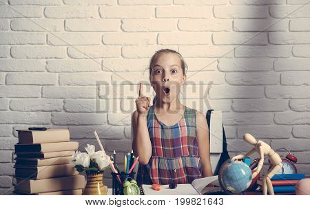 Schoolgirl Having New Idea Sits At Her Desk