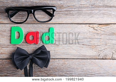 Word Dad With Glasses And Bow Tie On Grey Wooden Table