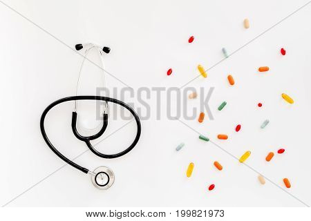 Medicine concept. Stethoscope and colored pills on white background top view.