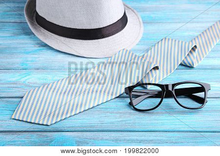 Necktie With Hat And Glasses On Blue Wooden Table