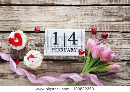 Tasty cupcakes with cube calendar and tulips on brown wooden table