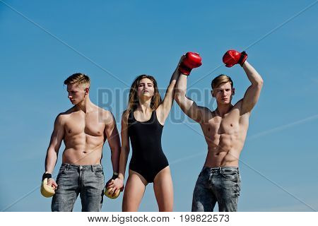 Boxer workout and healthy fitness. Woman and twins with muscular body. Sport people or team work. Men and coach sunny outdoor on blue sky. Winner and loser in boxing gloves with girl.