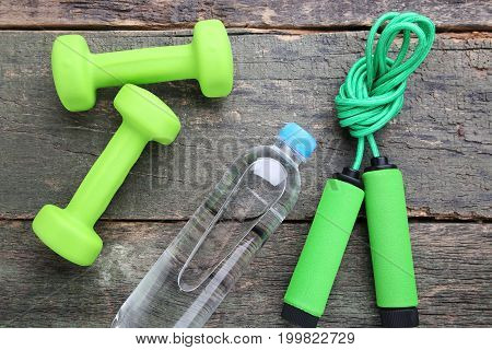 Green Skipping Rope With Bottle Of Water And Dumbbells On Wooden Table