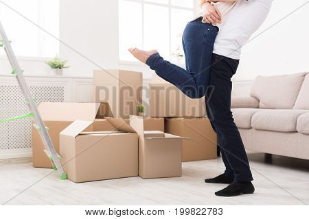 Crop of happy couple hugging near unpacked boxes in new apartment, copy space
