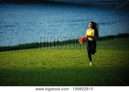 Girl sunny outdoor with fitness mat. Sport and sportswear fashion. Coach or trainer at workout. Woman running on green grass. Runner and success.
