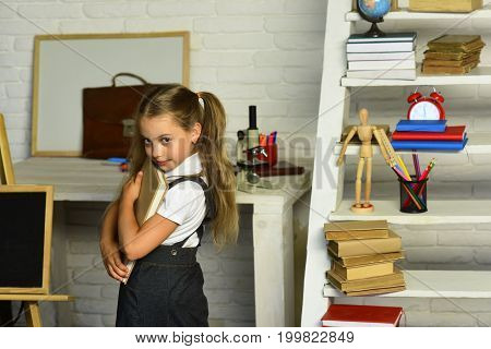 Schoolgirl With Ponytails Holds Book On Light Classroom Background