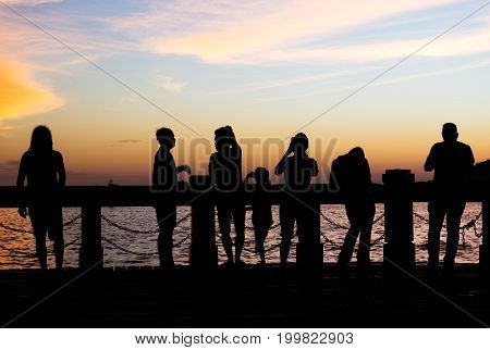 Silhouettes Of A Crowd Watching Sunset In Kota Kinabalu City Waterfront, Sabah Borneo, Malaysia.