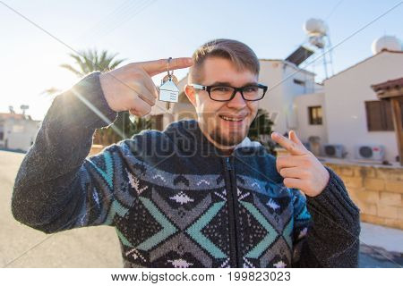 Young smiling man showing keys to new home. Real estate, apartment and people concept.