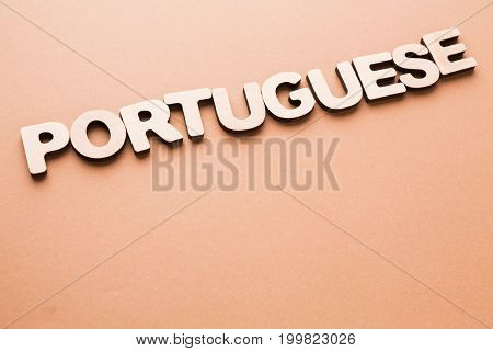 Word Portuguese on beige background. Foreign language learning, education concept