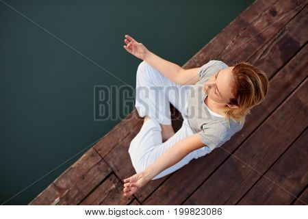 Top view of girl in yoga position near water on dock