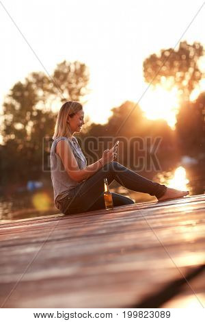 Girl sitting on dock by the river at sunset and looking at phone