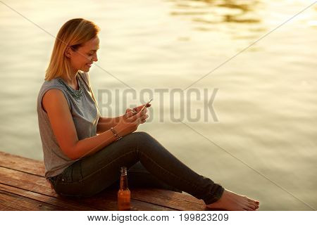 Young smile woman sitting on dock and looking at celphone