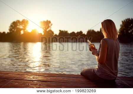 Woman enjoy in piece on sunset by river - back view