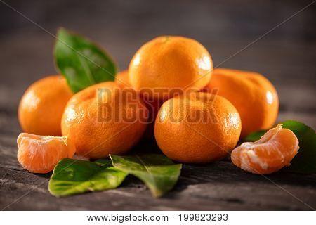 mandarines, peeled tangerine and tangerine slices on wooden table