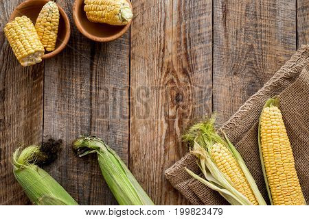 Organic farm food. Cutted corn cobs on rustic wooden background top view.