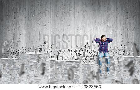 Young man in casual clothing sitting among flying letters with grey wall on background. Mixed media.