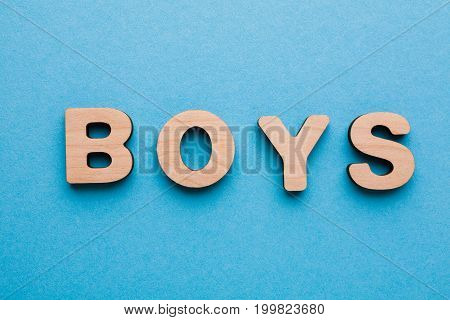 Word Boys made of wooden letters on blue background. Baby waiting concept