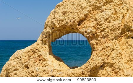 View through a hole in a Rock and an Aircraft above the blue Ocean. Close-up of a hole in a Rock. View to the Ocean.