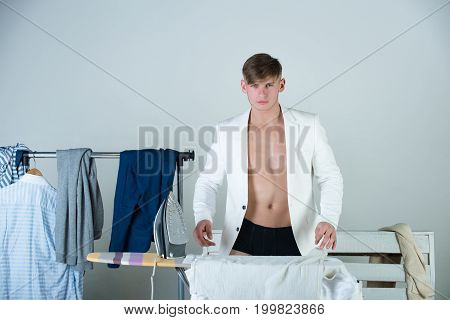 Macho wearing white jacket. Clothes hanging on rack on grey background. Athlete with muscular torso and chest. Housework and fashion concept. Man ironing shirt with iron.