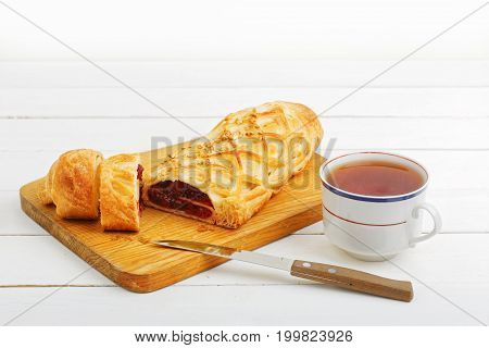 Homemade cherry strudel sprinkled with crushed nuts lying on a cutting board near a kitchen knife and cup of tea on a white wooden table.