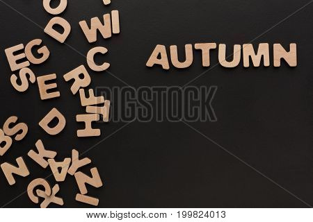 Word Autumn with heap of wooden letters on black background. Season learning, education concept
