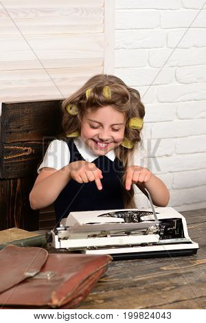 Small Girl With Curler In Hair With Typewriter.