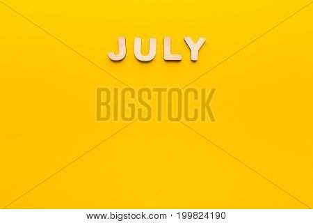 Word July made of wooden letters on yellow background. Month planning, timetable concept