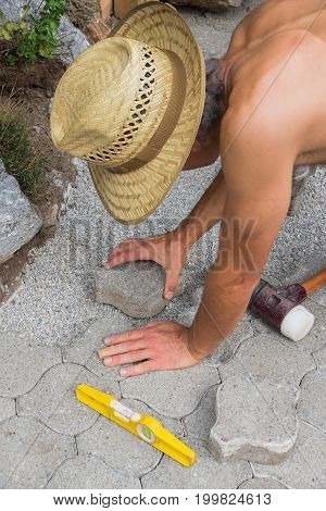 Gardener Fitting Flagstone In Pavement
