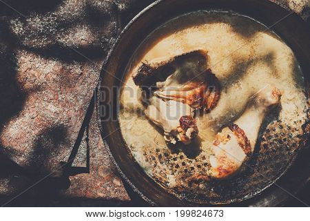 Chicken thighs in pan on rustic wooden table. Chicken baked outdoor at ecological farm. Natural food concept.